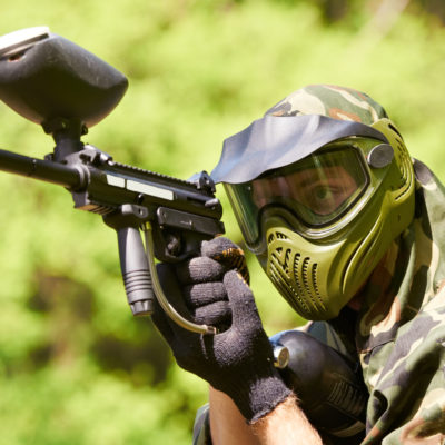 paintball sport player in protective uniform and mask aiming gun before shooting in summer